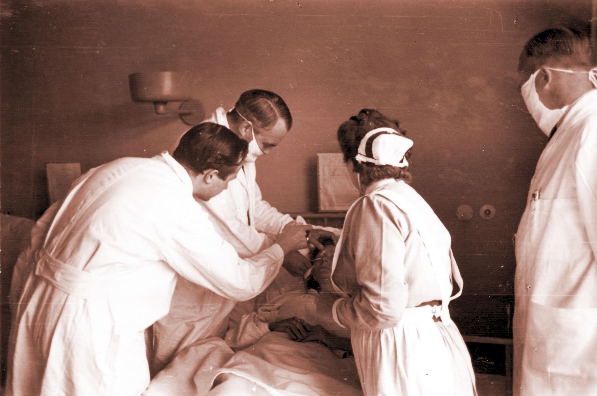 Professor Sven Larsson undersöker en sängliggande patient år 1947.